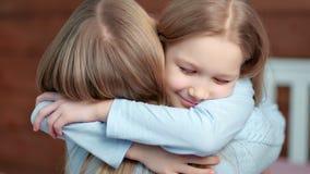 Närbildframsidan av litet behandla som ett barn flickan ger den stora kramen till hennes moder- och stänga sigögon för nöje lager videofilmer