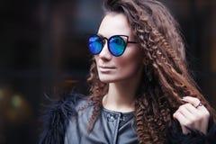 Närbildframsidastående av den unga härliga kvinnan med perfekt hud i solglasögon för öga för katt` s i cityscapen Härlig le flick royaltyfria foton