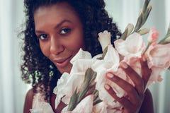 Närbildframsidaståenden av kvinnliga hållande gladioluses vänder mot nästan royaltyfri foto