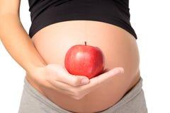 Närbildgravida kvinnan rymmer ett rött äpple royaltyfri foto