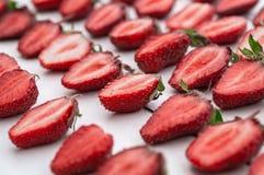 Närbildhög av nya högg av jordgubbar på vit bakgrund Hög många av den organiska mogna skivade jordgubben royaltyfria bilder