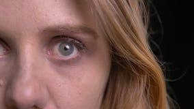 Närbildhalva-framsida stående av den gulliga blonda modellen som uppmärksamt och fast håller ögonen på in i kamera på svart bakgr arkivfilmer