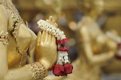 Närbildhand av den guld- statyn av Kinara på Wat Phra Kaew i Bangkok, Thailand Royaltyfria Bilder