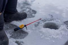 Närbildhanden av fiskarelås fiskar på vintermetspöet på den djupfrysta floden med hålet royaltyfria bilder