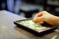 Närbildhandinnehav av räkningen med den thailändska pengarsedeln och mynt royaltyfri fotografi