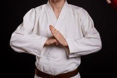Närbildkaratestudent på en svart bakgrund Kämpe i enhetligt visningavbrottstecken Karatekursbegrepp arkivfoto