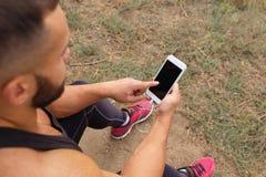 Närbildkroppsbyggare som kallar en telefon Muskulös man som använder teknologi på en suddig bakgrund Aktivt livsstilbegrepp Royaltyfri Bild