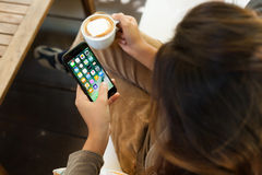 Närbildkvinna som rymmer nya den visande app-skärmen för iphone 7 i coffee shop Royaltyfri Fotografi