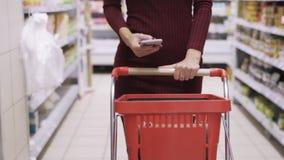 Närbildkvinnahänder rullar den röda vagnen i handla golv av supermarket och brukstelefonen arkivfilmer
