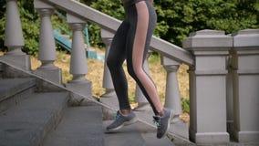 Närbildkvinnlign lägger benen på ryggen rinnande övre den utomhus- trappan lager videofilmer