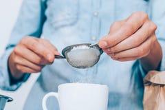 Närbildkvinnligns händer grundligt och siktar exakt mjöl arkivfoto
