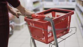 Närbildkvinnors händer rullar den röda vagnen i handla golv av supermarket, främre sikt lager videofilmer