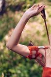 Närbildmakroskott av kvinnas hand som drar en pil för pilbåge från en darrning arkivfoto