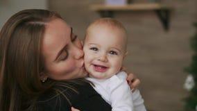 Närbildmamman kramar behandla som ett barn, och barnet ler se hans älskade moder Tillsammans ställning i det vita köket på lager videofilmer