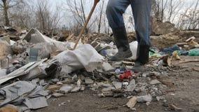 Närbildmannen lägger benen på ryggen att gå på platsen för avskrädeförrådsplatsen lager videofilmer