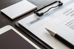 Närbildmeritförteckning, penna, digital minnestavla och affärskort på trä Arkivfoto