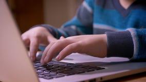 Närbildprofilfors av gulliga små pojkehänder som skriver på bärbara datorn arkivfilmer