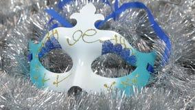 Närbildrotation av en karnevalmaskering på ett silverglitter Jul bakgrund, glitter lager videofilmer