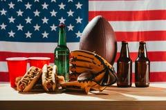 närbildsikt av öl med varmkorvar och sportutrustning med oss flagga Royaltyfria Foton