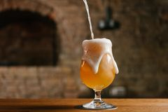 närbildsikt av att hälla nytt kallt öl med skum in i exponeringsglas i stång arkivfoton