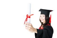 Närbildsikt av att le studenten i hållande diplom för avläggande av examenkappa Royaltyfria Foton
