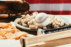 närbildsikt av baseballslagträn, baseballbollen på plattan med jordnötter, mellanmål och läderhandsken på trätabellen med oss fla Arkivbild