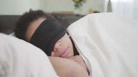 Närbildsikt av den attraktiva afrikansk amerikankvinnan som sover under den vita filten i svart sova maskering tr?ttad flicka stock video