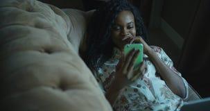 Närbildsikt av den gladlynta unga afro--amerikan kvinnan som skrattar och pratar genom att använda mobiltelefonen, medan ligga på lager videofilmer