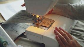 Närbildsikt av den moderna elektriska symaskinen som arbetar sy stycket av tyg Manicured hand för flicka` s och färgrikt stock video