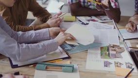 Närbildsikt av den multietniska grupp människor som arbetar på tabellen Det idérika affärslaget väljer färgen och materialet arkivfilmer
