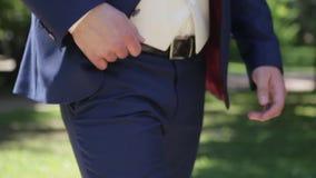 Närbildsikt av den okända säkra brudgummen i blåttdräkten som sätter handen i fack, medan promenera parkera arkivfilmer