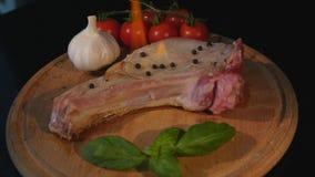 Närbildsikt av det rå stycket av kött- och chilipeppar med flamman på svart skärbräda flammor för bbq för gallernötköttbiff stock video