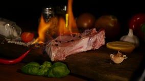 Närbildsikt av det rå stycket av kött- och chilipeppar med flamman på svart skärbräda flammor för bbq för gallernötköttbiff lager videofilmer