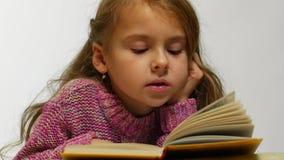 Närbildsikt av en flicka som läser en bok En ung gullig flicka läser en bok i en viskning lager videofilmer