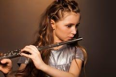 Närbildsikt av flickan som spelar på silverflöjten arkivfoto