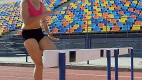 Närbildsikt av flickor som hoppar lätt över hinder, häcklopp, konkurrens arkivfilmer