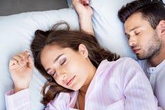 närbildsikt av härliga unga par, i att sova för pyjamas arkivfoto