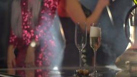 Närbildsikt av handen som häller champagnen in i exponeringsglas på den suddiga bakgrunden av dansflickvännerna stock video