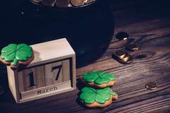 närbildsikt av kalendern, kakor i form av treklövern och krukan med guld- mynt på trä royaltyfri illustrationer
