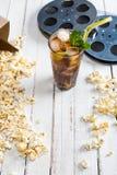 Närbildsikt av popcorn med med is te i exponeringsglas- och filmrullar på tabellfilmtid royaltyfri fotografi
