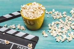Närbildsikt av popcorn och filmclapperen på träbegrepp för tabellfilmtid arkivbilder