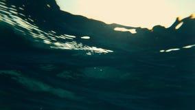 Närbildsikt av solen under vattnet, till och med ett lager av vatten Undervattens- sikt av havsyttersidan, strålar av solljus stock video