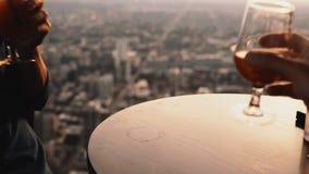 Närbildsikt av två coctailar som står på tabellen i restaurang i skyskrapa kvinna för datummanromantiker stock video