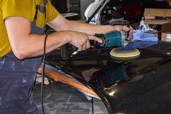 Närbildsikt på händerna av en manlig arbetare i den gula skjortan som rymmer ett hjälpmedel för att polera huven av en bil, medan royaltyfria bilder