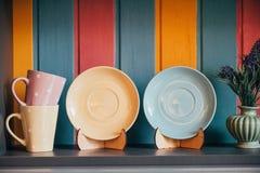 närbildsikten av dekorativt tömmer plattor och koppar nära den färgrika väggen i restaurang royaltyfri bild