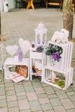 Närbildsikten av den älskvärda bröllopsammansättningen av de tappningstearinljusställningarna och spjällådorna dekorerade med blo Royaltyfria Bilder