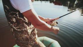 Närbildsikten av manhänder använder stången med snurrrullen Fisher man som spenderar tid i naturen bara arkivfilmer