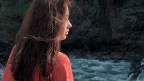 Närbildsikten av unga flickan i rött klänninganseende nära att slå för stormvågor vaggar unga flickan som ut ser till havet lager videofilmer