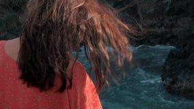 Närbildsikten av unga flickan i rött klänninganseende nära att slå för stormvågor vaggar unga flickan som ut ser till havet stock video