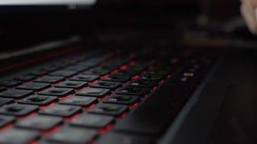 Närbildsikten fingrar det knackande lätt på tangentbordet av bärbara datorn och skrivameddelandet arkivfoton